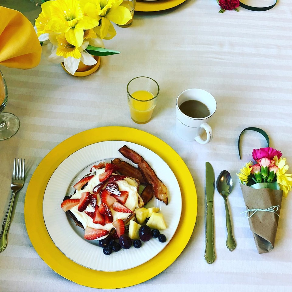 Mothers Day breakfast table setting, orange juice, lemon cream french toast, berries, bacon, and a bouquet of flowers